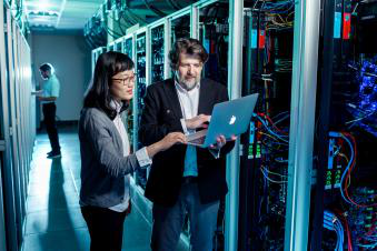 Two people looking at a computer in a server warehouse