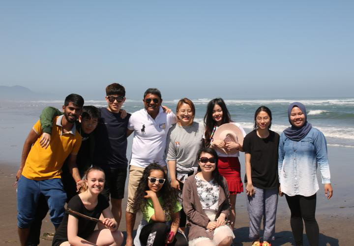 PSU international students standing as a group on the beach.