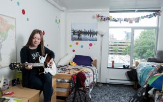 Female student playing guitar in her dorm room
